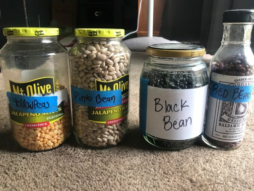 Yellow peas, pinto beans, black beans and red beans in individual glass jars.