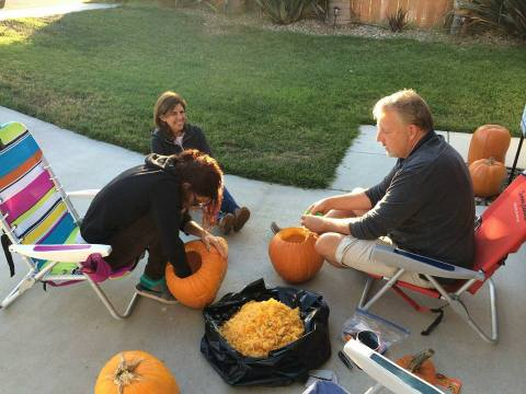 photo of a family carving pumpkins