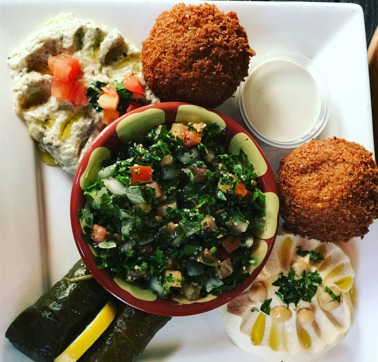 The Vegetarian Plate at The Garden - tabbouleh, falafel, baba ganoush, hummus, pita, and a tahini sauce.