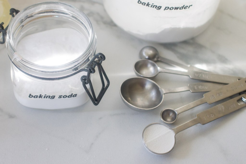 Baking soda and baking powder in canisters with measuring spoons on counter.