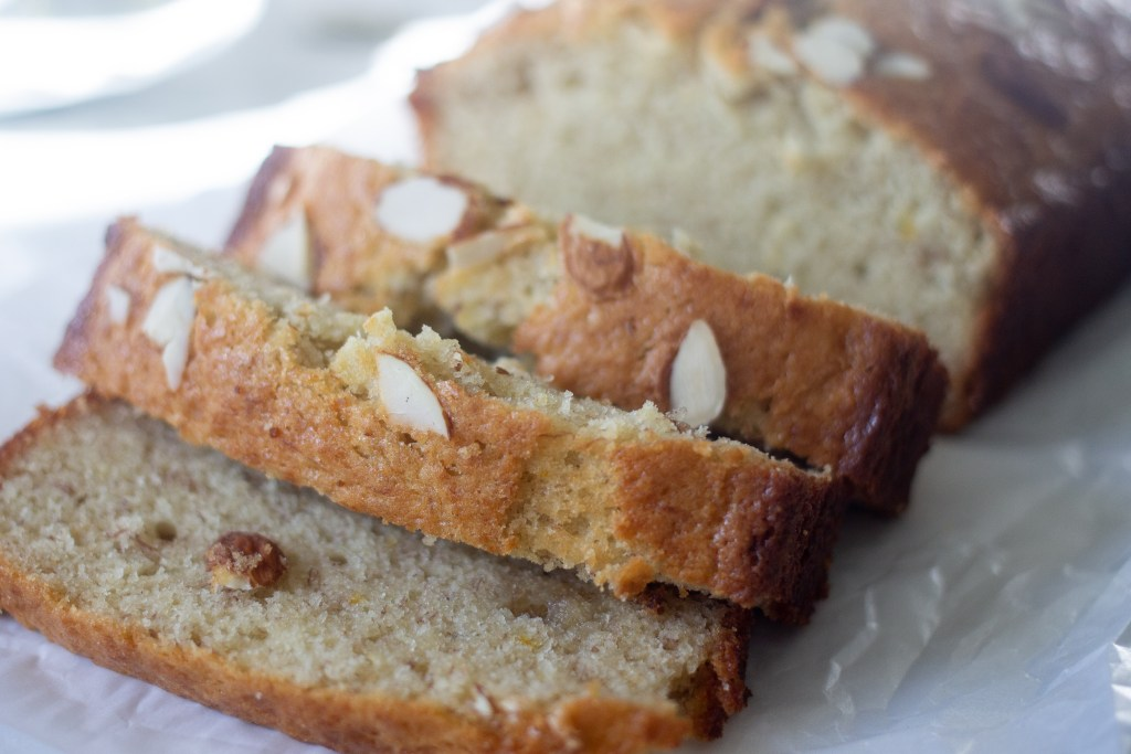 Banana bread with sour cream, with almond slices sprinkled on top.