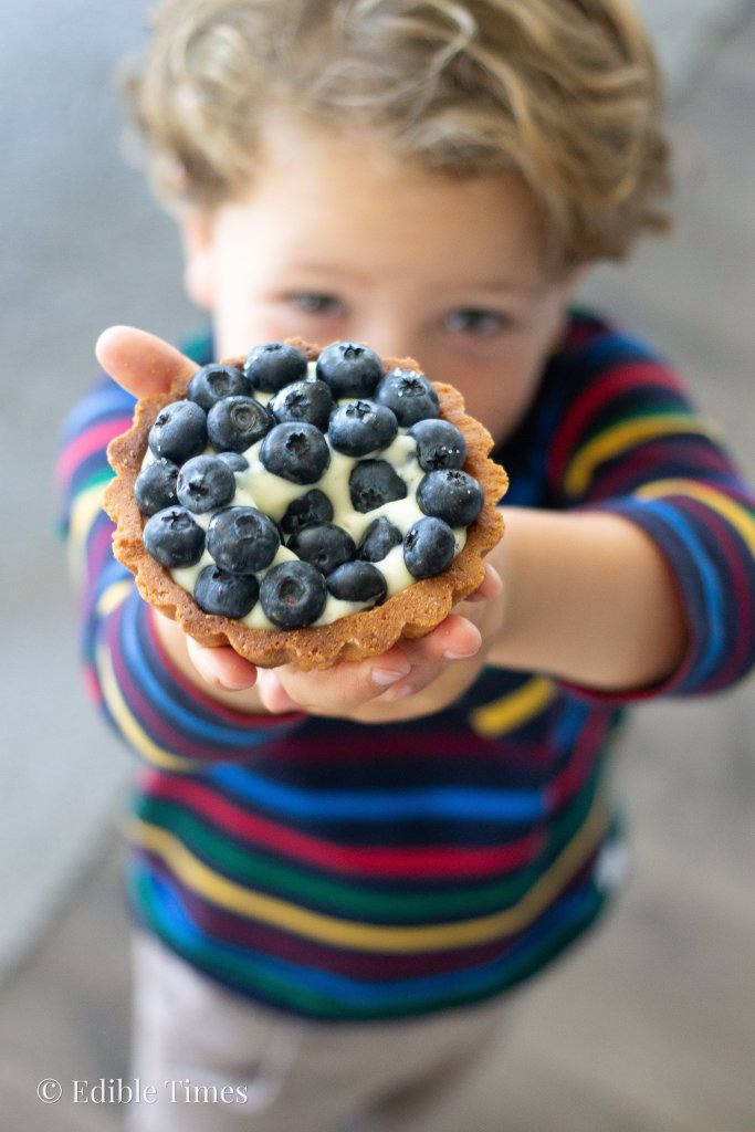 Little boy holding up fresh fruit tart.