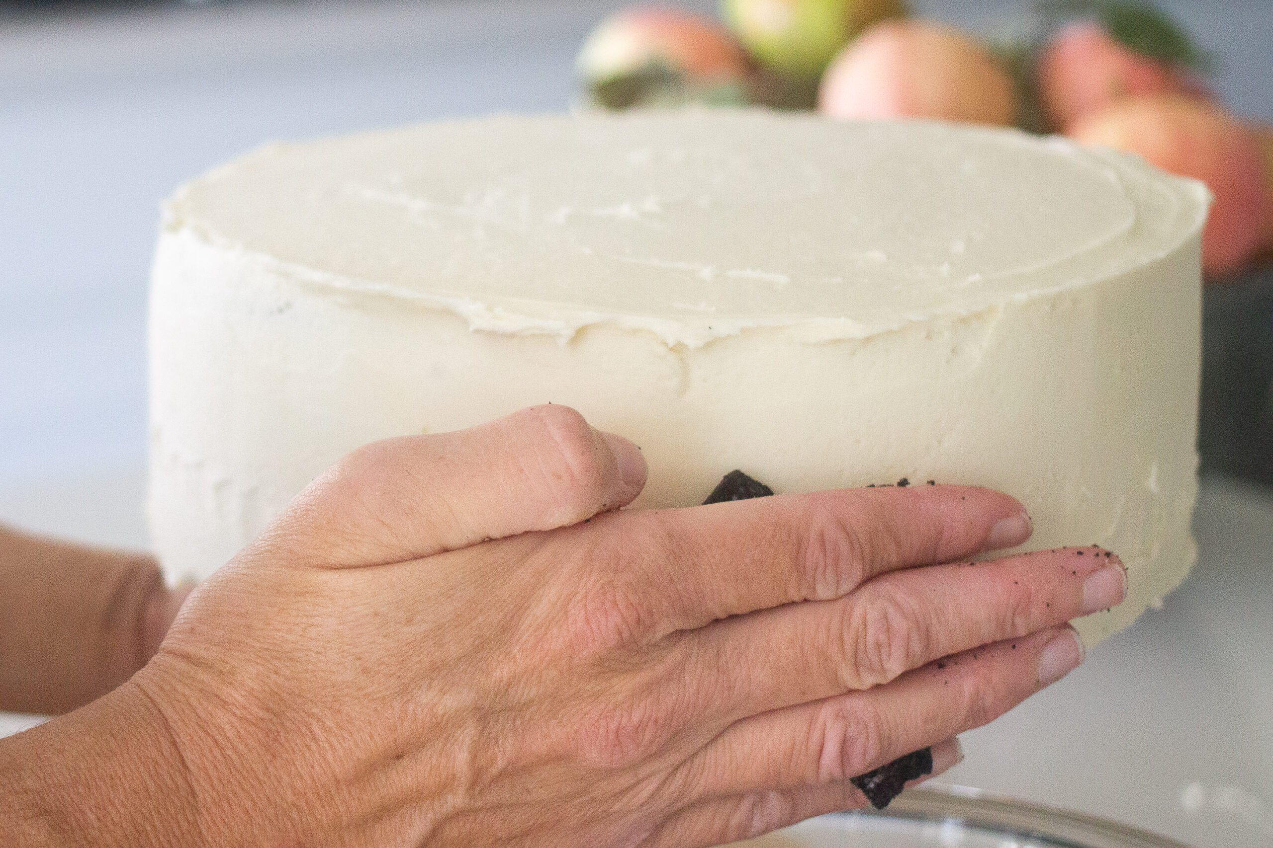 Hand placing cookie crumbs on side of cake.