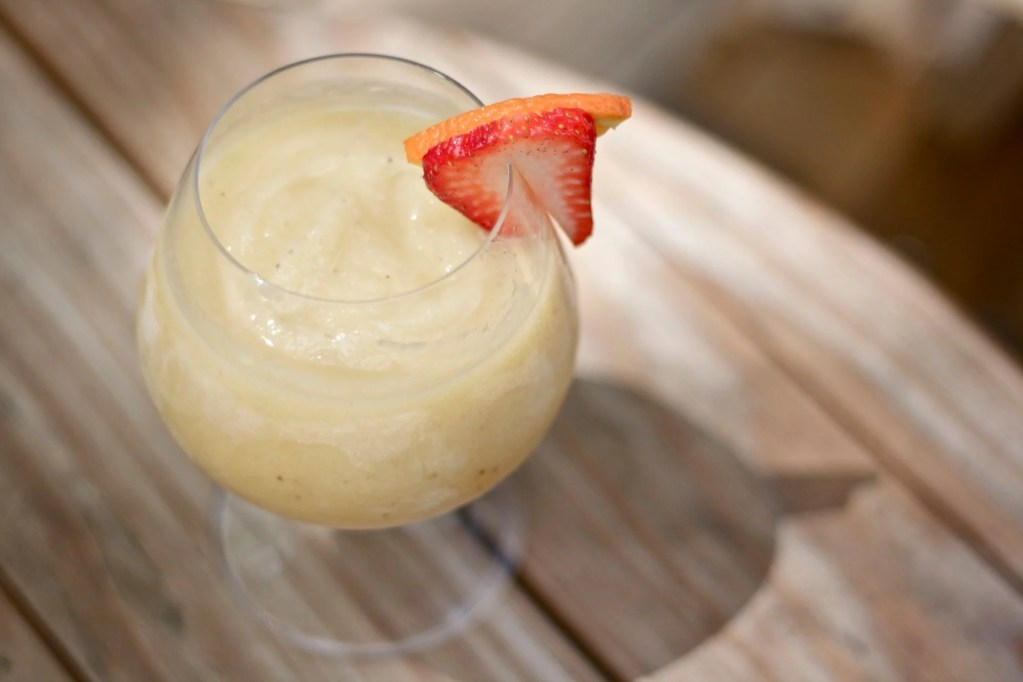 Frozen banana daiquiri garnished with fruit on table.