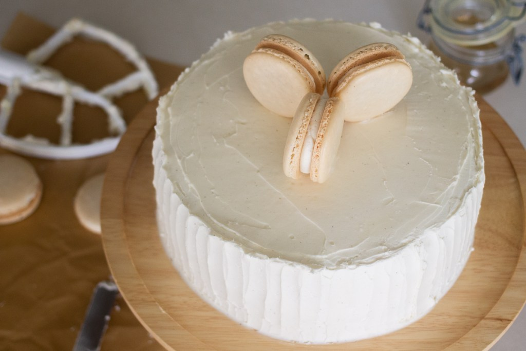 Vanilla French macarons on top of vanilla bean round layer cake.