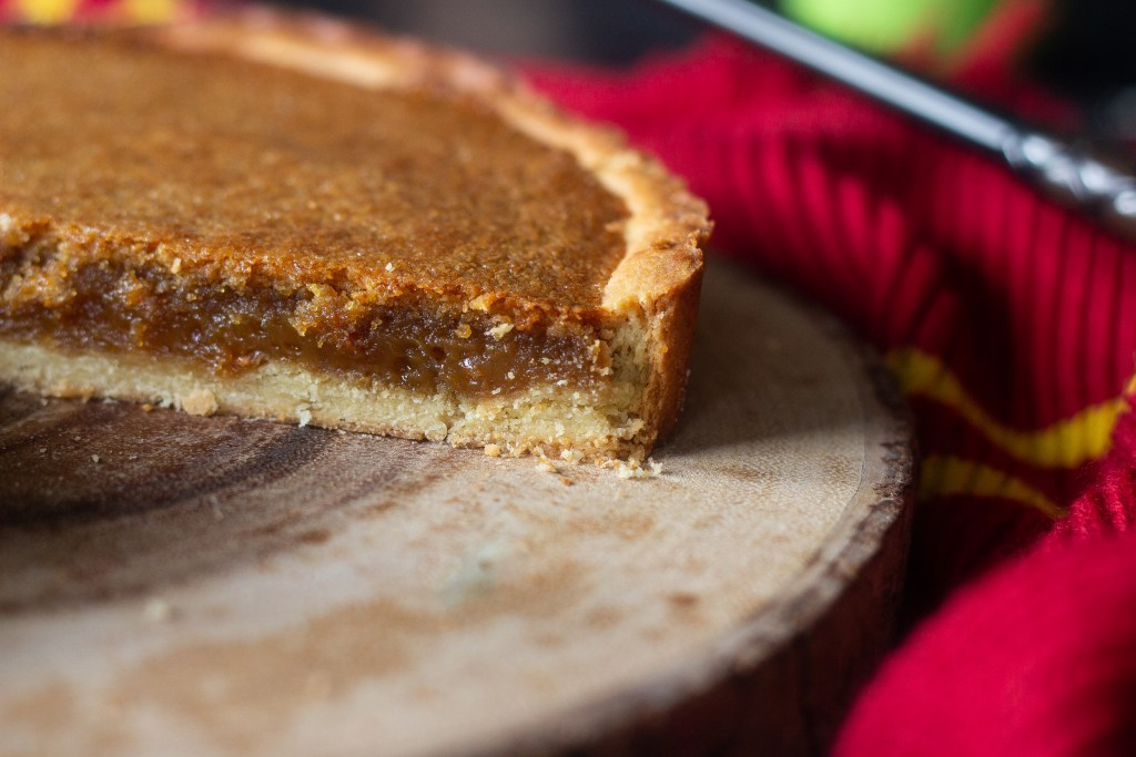 Close up of treacle tart crust on wooden charger.