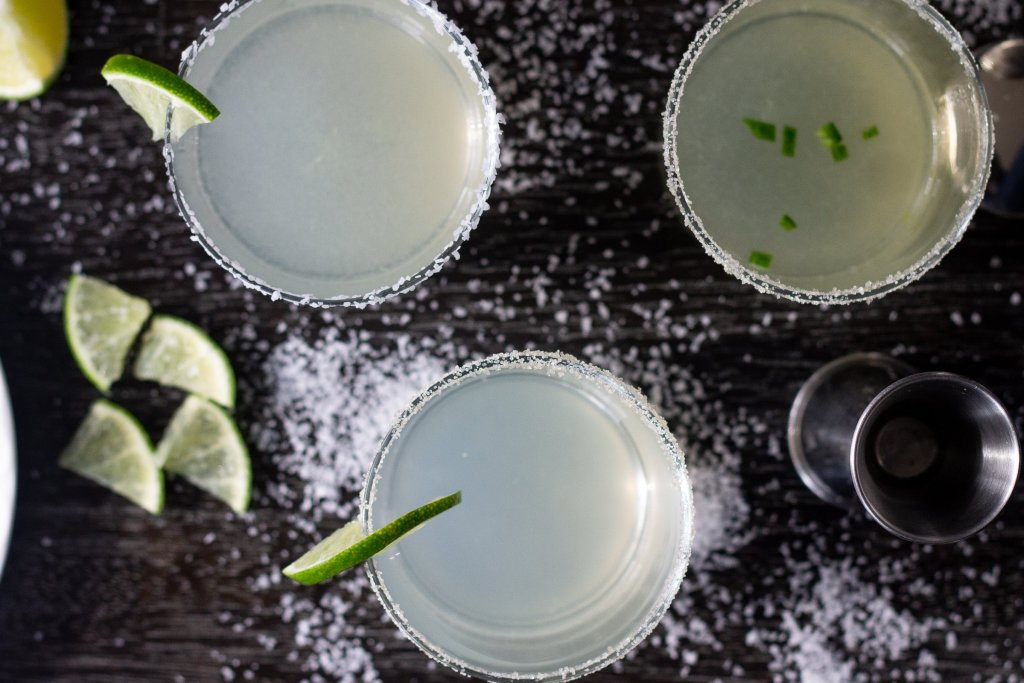 Three margaritas on a table with salt and lime wedges.