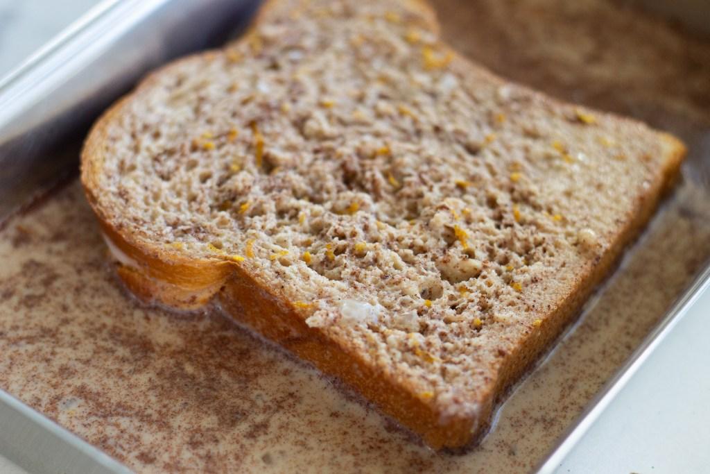 Slice of brioche bread soaking in French toast batter.
