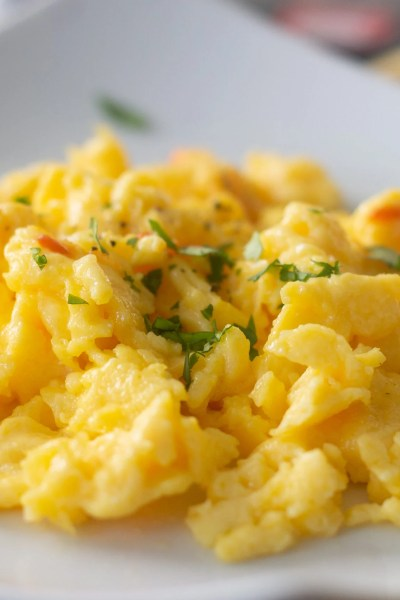 Close up of scrambled eggs with sharp cheddar cheese, cilantro, sriracha on plate