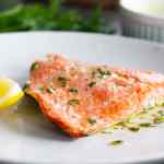 Lemon and herb roasted sockeye salmon on white plate with lemon.