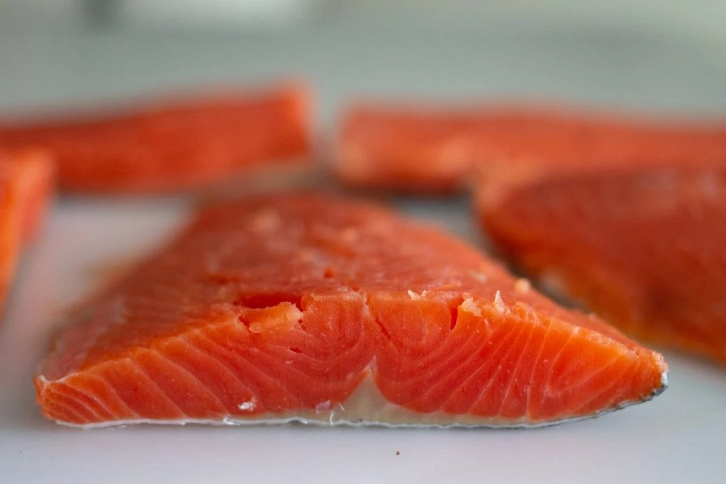 Close up of sockeye salmon fillet on cutting board.
