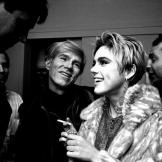 black-and-white photograph of Andy Warhol and Edie Sedgwick laughing and talking to people.