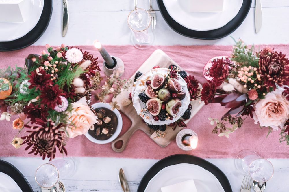Formal Table setting with red and pink flowers, candles, black and white dishes and a fig cake.