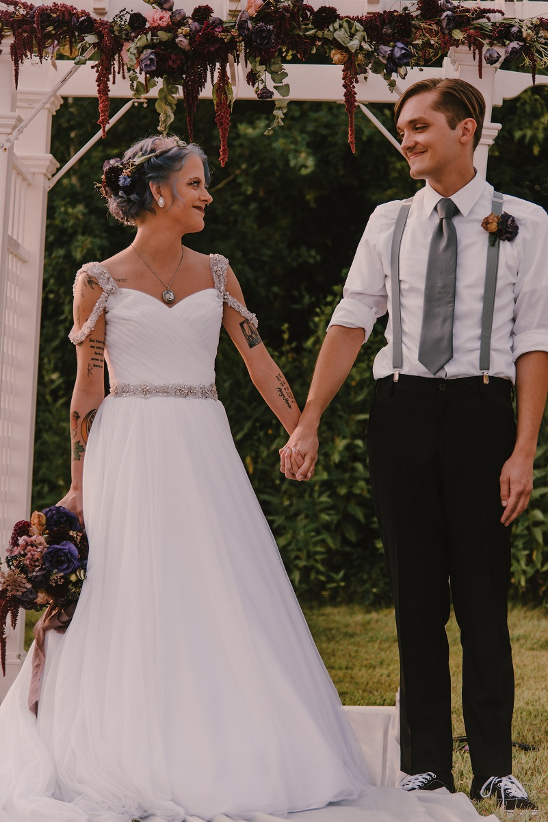 White woman and man holding hands at a wedding altar.