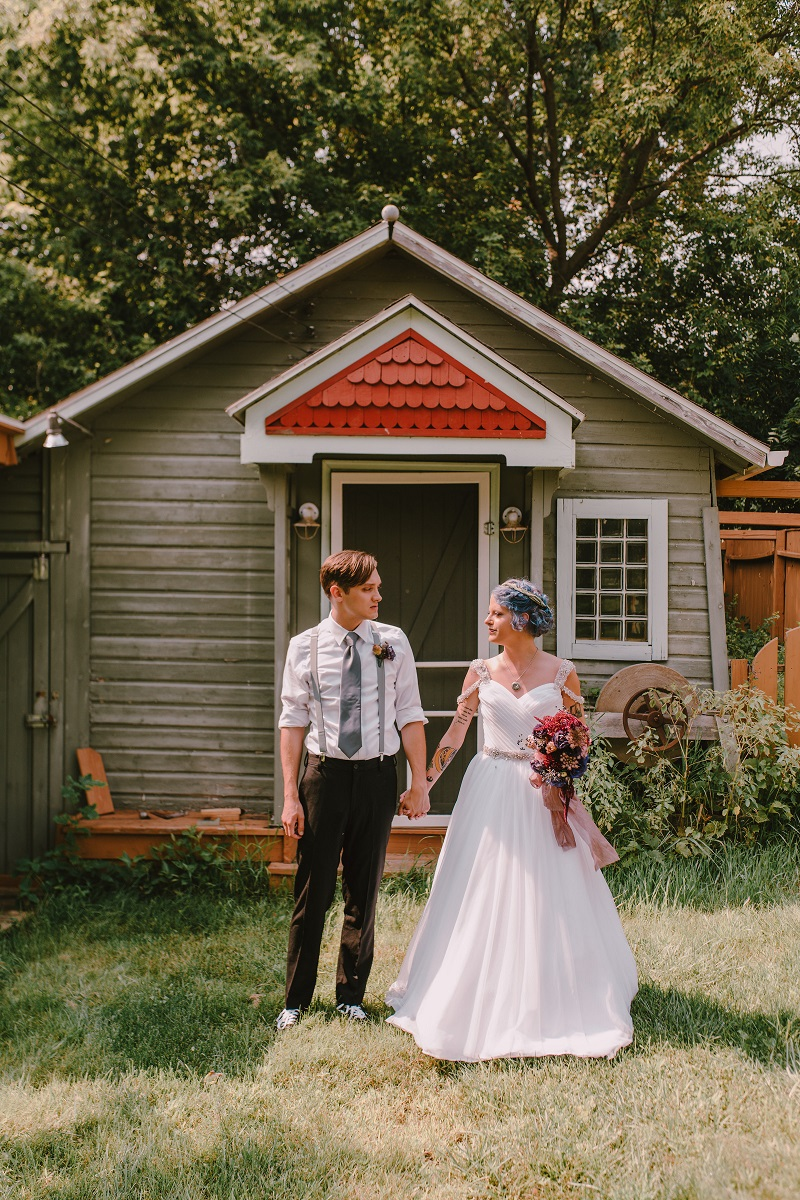 Bride and Groom holding hands in front of a small cabin. Woman holding dark flower bouquet in summer.