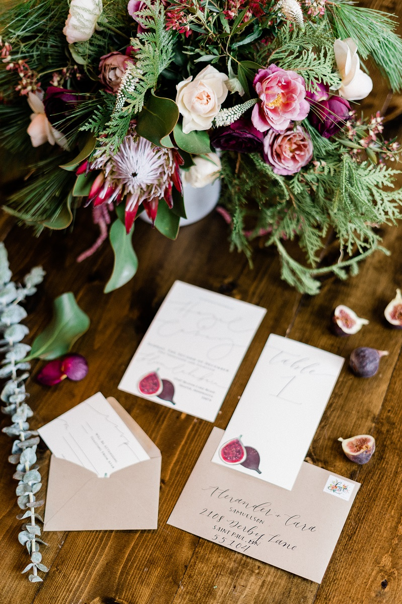 Wedding invitations and a floral bouquet styled in a flatlay photo.
