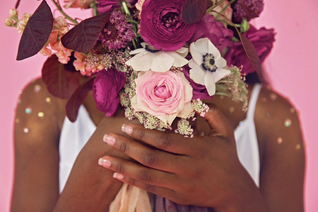 Dark-skinned person's hands holding pink and white flowers.