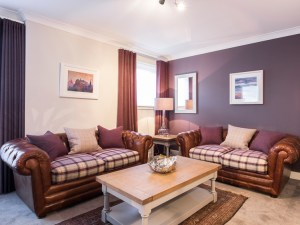 The Botanist Apartment (formerly named Parkgate Residence Edinburgh) tartan and leather sofas in living room
