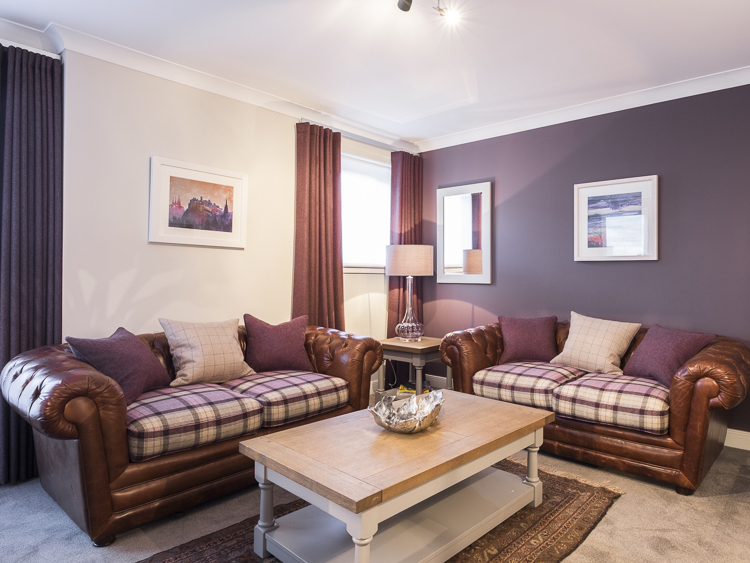 Living Room in the Parkgate Residence Edinburgh showing leather sofas and soft furnishings in mauve wood tweeds and plaids.