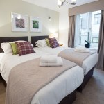 The McDonald Residence Superking or Twin Bedroom showing modern plaid cushions and photographic artwork