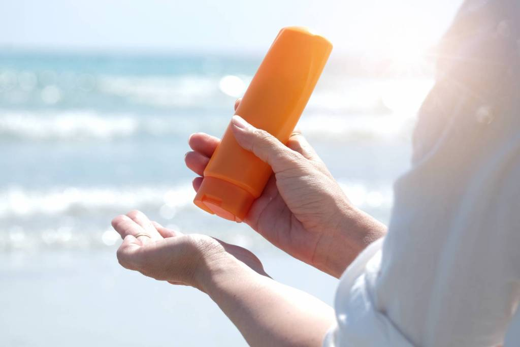 Canva Hand Of Female Holding Sunscreen. Very Sun Light Sky Background.Health Concepts And Skin Care