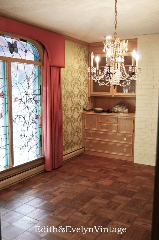 The formal dining room with original parquet floors, built in hutch, brick wall, and stain glass window.
