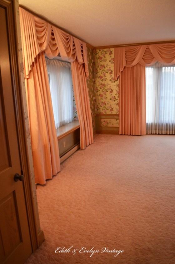 Pink shag carpet, pink drapes, pink rose wallpaper.
