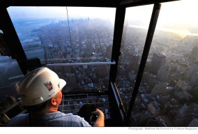 Crane operator Danny Dunn watches the sun rise over Manhattan. His crane atop the tower, is about six stories higher then the roof the building.