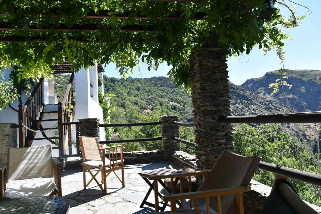 writers retreat in Spain Spanish patio with wisteria climbing over trellis and view of mountains