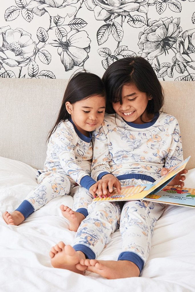 two kids in This is J PJ set reading on the bed