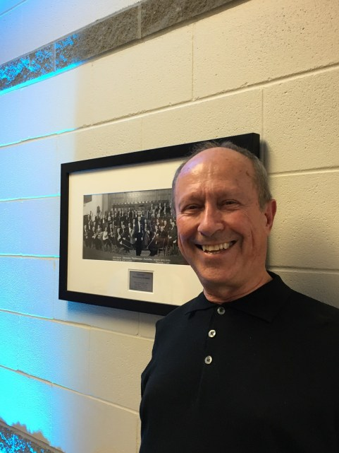 ESO Violinist Brody Olson stands next to a photo from the 1940s, when his father performed with the orchestra.
