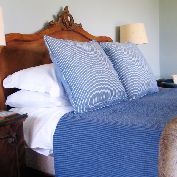 French walnut bed dressed with striped cushions