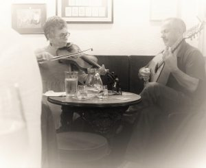 Traditional celtic players with fiddle and guitar in a pub