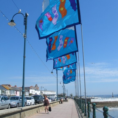 Bright blue flags flying in teh breeze on Penzance promenade
