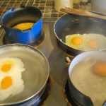 breakfst eggs cooking on a stove four ways - scrambled, fried, poached and boiled
