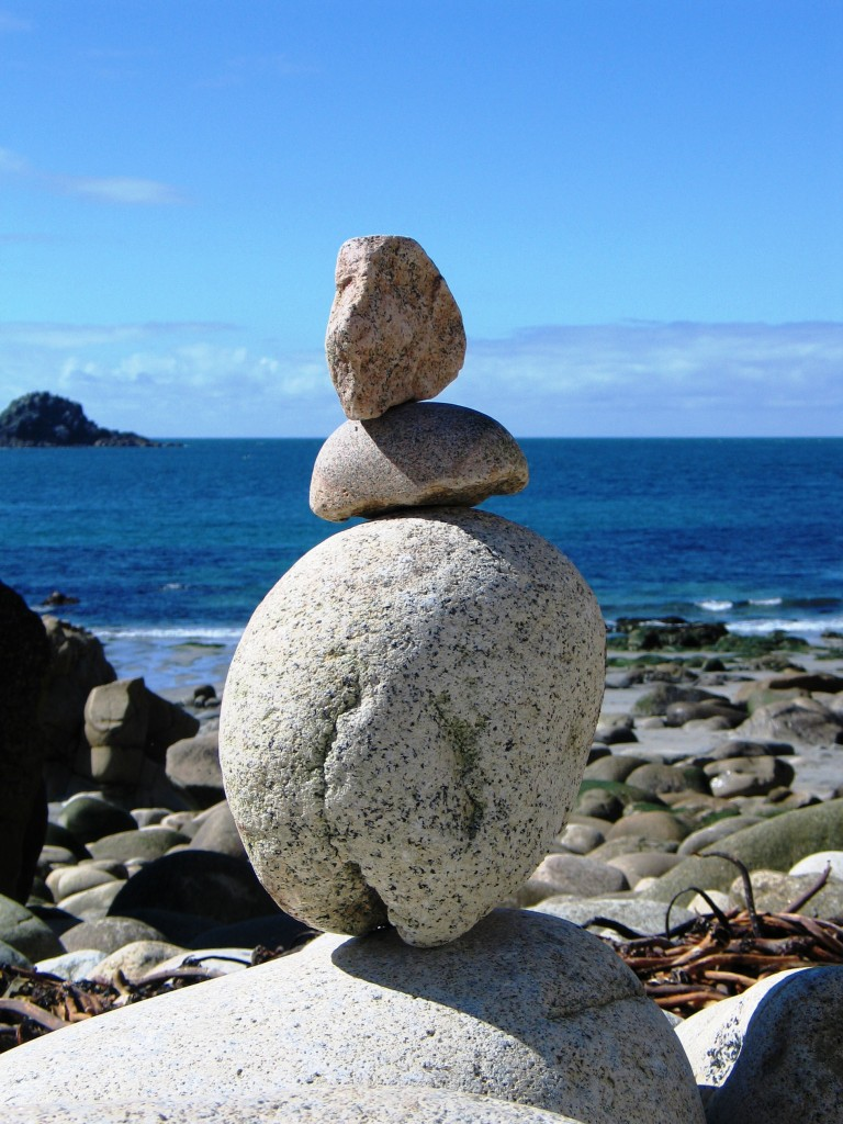 Rock art using the egg shaped boulders of Cot Valley framed by blue sky and sea
