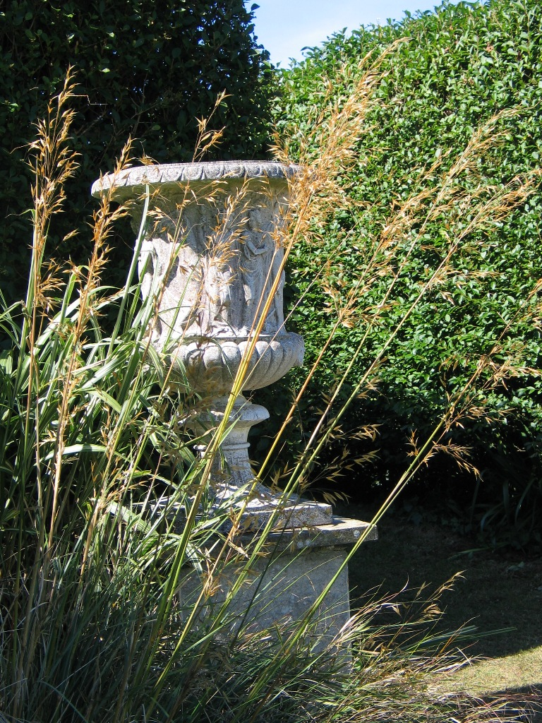 Golden oat grass flanks the urns at th entrance to the Italian Garnden