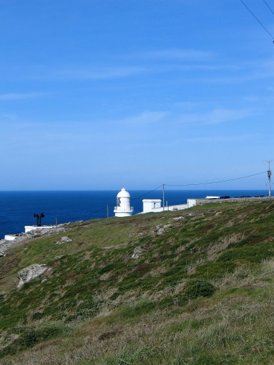 Startlingly white Pendeen lighthouse glimpsed over he headland