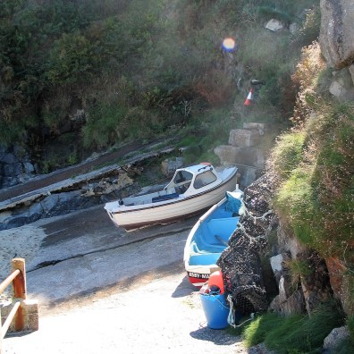Fishing boats and lobster pots pulled up in Boat Cove near Potheras Cove