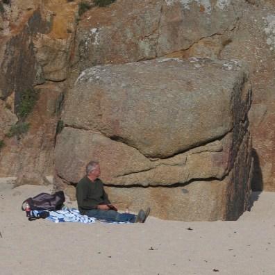 single figure sitting on the sands