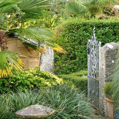 Stone mushrromm and grantie gatepost frame an entrance to a formal garden