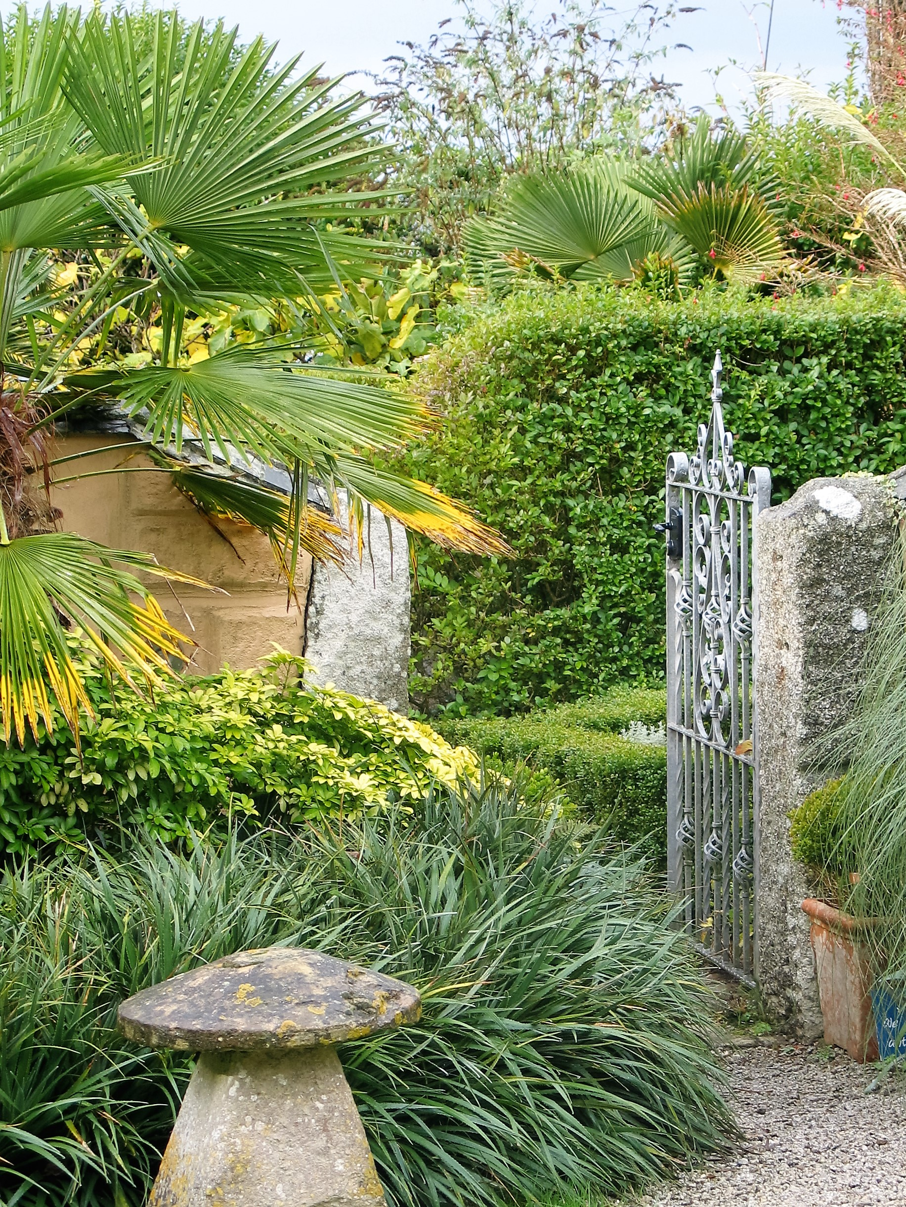 Stone mushrromm and grantie gatepost frame an entrance to a formal garden