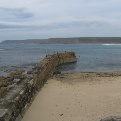 The worn harbour arm stretching into the sea