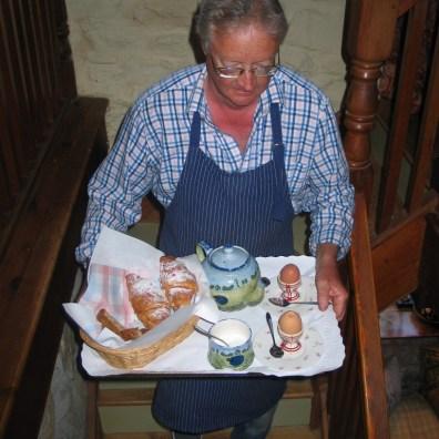 croissants,eggs and tea pot on a tray