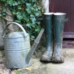 galvanised watering can and wellington boots beside a door