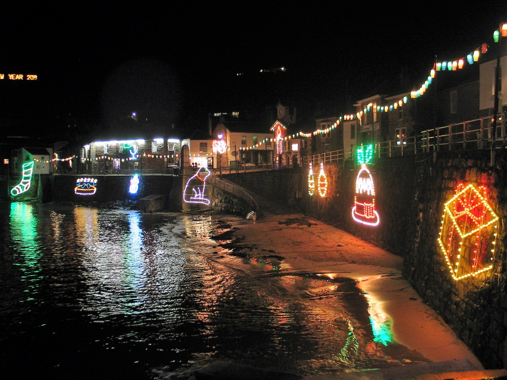 tide on harbour slip with reflecting Christmas lights