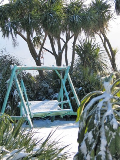 Garden swing in the snow - february's golden spring turns to snow and ice