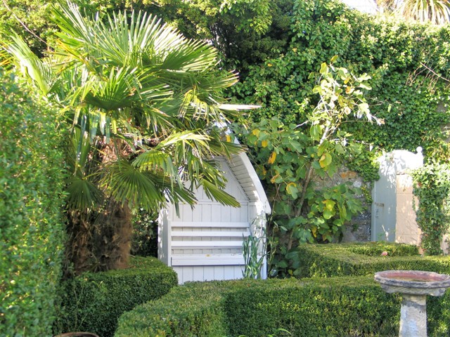 White garden arbour flanked by fig and palm in formal courtyard - september garden