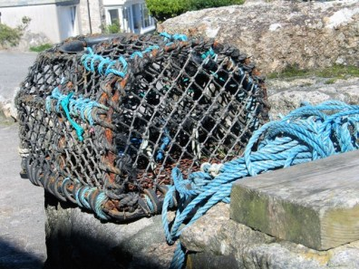 Lobster pot on a granite harbour wall -Lamorna