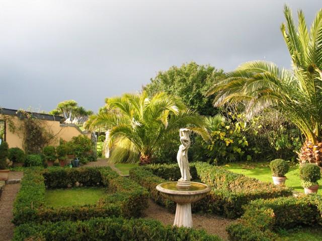 Dramatic November sky over Mediterranean style courtyard and fountain - Ednovean Farm